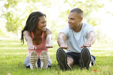 Woman and man outside stretching while sitting and looking at one another smiling